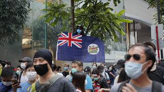 A man displays the Hong Kong colonial flag on the anniversary of Hong Kong's handover to China from Britain in Hong Kong, Wednesday, July. 1, 2020.