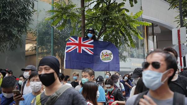 A man displays the Hong Kong colonial flag on the anniversary of Hong Kong's handover to China from Britain in Hong Kong, Wednesday, July. 1, 2020.