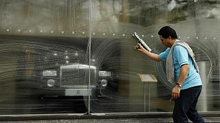 A window cleaner works on a window at a Rolls-Royce showroom in London