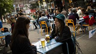 European tourists drinks beers at the terrace of the Bar du Matin restaurant in Brussels