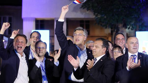 Croatia's Prime Minister incumbent Andrej Plenkovic (holding a Croatian flag) celebrates victory at the Archaeological Museum in Zagreb, on July 5. 2020.