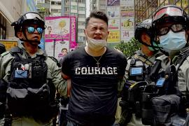 Police detain a protester after dispersing pepper spray during a protest in Causeway Bay before the annual handover to China march in Hong Kong. 1 July 2020