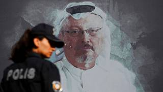 A Turkish police officer walks past a picture of slain Saudi journalist Jamal Khashoggi prior to a ceremony, near the Saudi Arabia consulate in Istanbull - Oct. 2, 2019 (file)