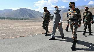 In this handout photo provided by the Press Information Bureau, Indian Prime Minister Narendra Modi walks with soldiers during a visit to the Ladakh area, India, Friday, July