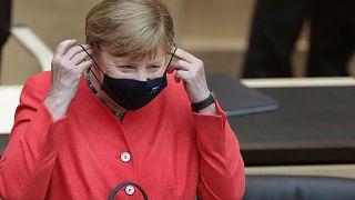 German Chancellor Angela Merkel adjusts her face mask