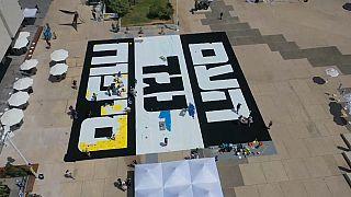 """صورة من الجو لمجسم يحمل عبارة بالعبرية: """"الشعب ضد الضم"""". تل أبيب - 2020/07/03"""