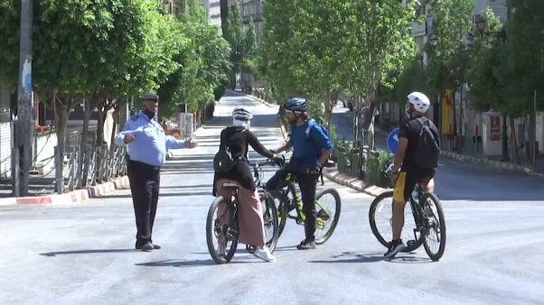 شرطي فلسطيني يتحدث مع مستعملي دراجات هوائية في رام الله - 2020/07/03