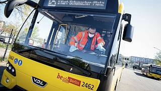 An employee wearing mouth and nose protection and protective gloves cleans the passenger area of a BVG bus at the terminal in Berlin, Germany, Wednesday, April 22, 2020.
