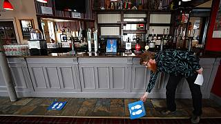 Owner Are Kjetil Kolltveit from Norway places markers for social distancing on the front of the bar at the Chandos Arms pub in London, Wednesday, July 1, 2020.