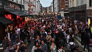 Revellers pack a street outside bars in the Soho area of London on July 4, 2020