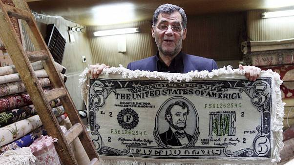 Iranian shopkeeper holds a carpet in a US five dollar note design in the main Bazzar in Tabriz