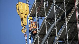 A worker operates at a construction site in Milan, Italy