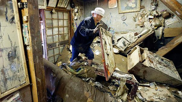 A man looks for his medicine at the house damaged by floods provoked by heavy rains in Hitoyoshi, Kumamoto prefecture, southern Japan. July 12, 2020