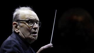 """In this file photo dated Tuesday, March 6, 2018, Italian composer Ennio Morricone directs an ensemble during a concert of his """"60 Year Of Music World Tour"""", in Milan, Italy"""