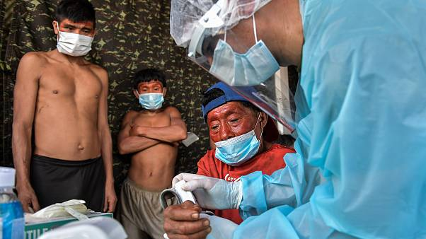 Members of the Brazilian Armed Forces medical team examine a person in the indigenous land of Suru