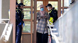 Polícia fala com uma residente de um complexo de apartamentos em confinamento em Melbourne