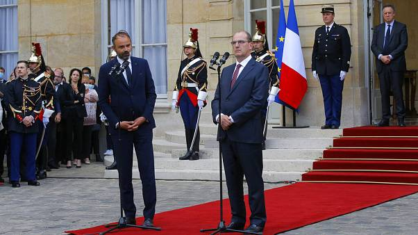 Outgoing French Prime Minister Edouard Philippe, left, speaks while newly named Prime Minister Jean Castex listens after the handover ceremony in Paris.