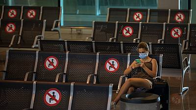 A passenger sits at Barcelona airport in Barcelona, Spain, Tuesday, June 30, 2020.