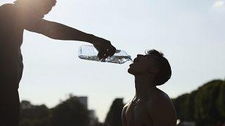 Un entrenador da agua a su estudiante durante una sesión de entrenamiento en un caluroso día de verano en Bruselas el 25 de junio de 2020.