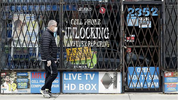 A man walks by a closed store during the COVID-19 in Chicago
