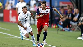 FC Dallas defender Ryan Hollingshead plays the ball while Minnesota United forward Miguel Ibarra chases him during the first half of an MLS soccer match in Frisco, Texas.
