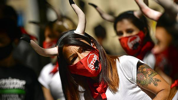 Demonstrators wear faces masks while protesting against San Fermin's bullfighting, canceled this year by the conoravirus pandemic, in Pamplona, northern Spain, Tuesday, July 7