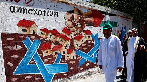 Hamas supporters pass a mural against Israel's plan to annex parts of the West Bank and U.S. President Donald Trump's mideast initiative