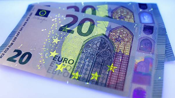 Two new 20 Euro bank notes are photographed under black light in Frankfurt, Germany