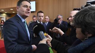 Irish Finance Minister Paschal Donohoe, left, speaks with the media prior to a meeting of the eurogroup at the EU Council building in Brussels on Monday, Feb. 19, 2018.