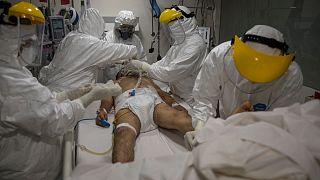 Médicos y enfermeras atienden a un paciente dentro de la unidad de cuidados intensivos para casos de COVID-19 en el hospital privado Ricardo Palma, en Lima, Perú.
