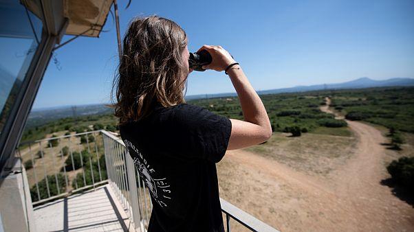 Camille Mollier, étudiante, observe les environs avec des jumelles depuis la vigie de l'Arbois près d'Aix-en-Provence dans le sud de la France, le 7 juillet 2020