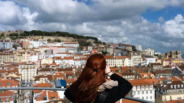 A woman takes pictures from the top of Lisbon
