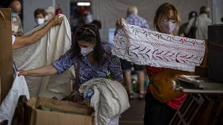 Customers wearing face masks pick second hand fabrics in a market in Barcelona on Wednesday, July 8, 2020.