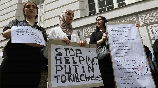 "Chechen protesters hold a banner that reads ""Stop helping Putin to kill Chechens"" outside of the Russian embassy in Vienna on Tuesday"