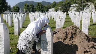 A woman kisses a grave stone in Potocari, near Srebrenica, Bosnia, Saturday, July 11, 2020. Nine newly found and identified victims of the 1995 genocide were laid to rest.