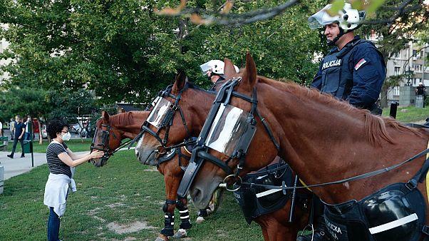 A rohamrendőrség lovát kényezteti egy járókelő Belgrádban