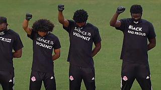 شاهد:  لاعبون أمريكيون لكرة القدم يشجعون المساواة العرقية بمقابض الأيدي وطي الركب