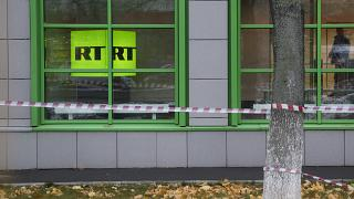 Russian state-owned television station RT logo is seen at the window of the company's office in Moscow, Russia, Friday, Oct. 27, 2017.