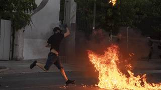 A protester throws a petrol bomb at riot police outside the Greek Parliament during a demonstration against new protest law in Athens, on Thursday July 9, 2020.