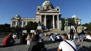 People sit during a protest in front Serbian Parliament building in Belgrade, Serbia,Thursday, July 9, 2020.