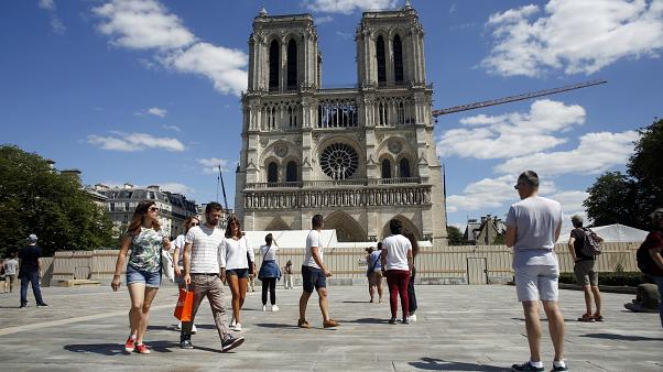 People walk on the forecourt of Notre Dame's Cathedral, in Paris, Sunday, May 31, 2020.