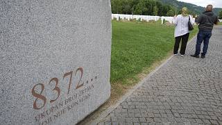 """Visitors pray at the memorial cemetery in Potocari, near Srebrenica, Bosnia, Tuesday, July 7, 2020. Writing on stone translates """"8372 victims, number is not final'."""