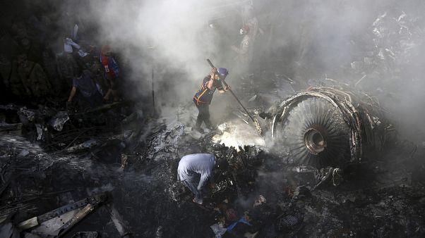 In questa foto del 22 maggio 2020, un volontario cerca superstiti tra i rottami del volo Pakistan International Airlines schiantatosi a Karachi