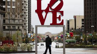"A person wearing a protective face mask and gloves as a precaution against the coronavirus walks by the Robert Indiana sculpture ""LOVE"" at John F. Kennedy Plaza,"