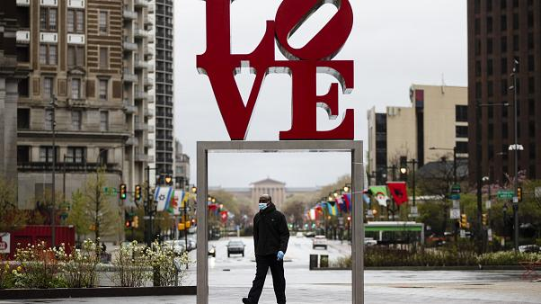 """A person wearing a protective face mask and gloves as a precaution against the coronavirus walks by the Robert Indiana sculpture """"LOVE"""" at John F. Kennedy Plaza,"""