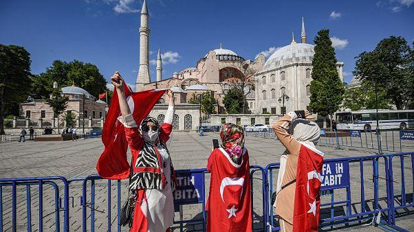 Ciudadanos envueltos en la bandera turca celebran la conversión de la basílica de Santa Sofía en mezquita
