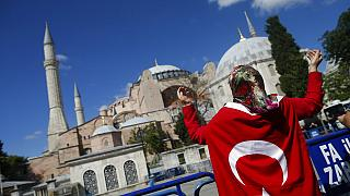 People, draped in Turkish flags, chant slogans, outside the Byzantine-era Hagia Sophia