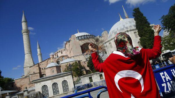 People, draped in Turkish flags, chant slogans, outside the Byzantine-era Hagia Sophia