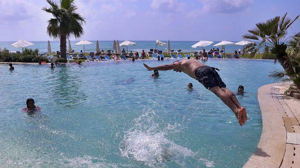رجل يقفز في مسبح في منتجع في الرميلة جنوب العاصمة اللبنانية بيروت - 2020/06/20