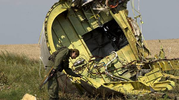 In this July 22, 2014 file photo, a pro-Russian rebel touches the MH17 wreckage at the crash site of Malaysia Airlines Flight 17, near the village of Hrabove, eastern Ukraine.